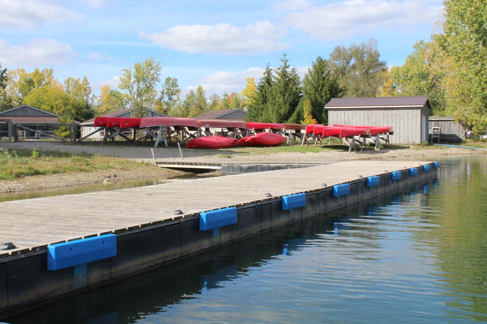 dock and canoes next to lake at camp trillium rainbow lake